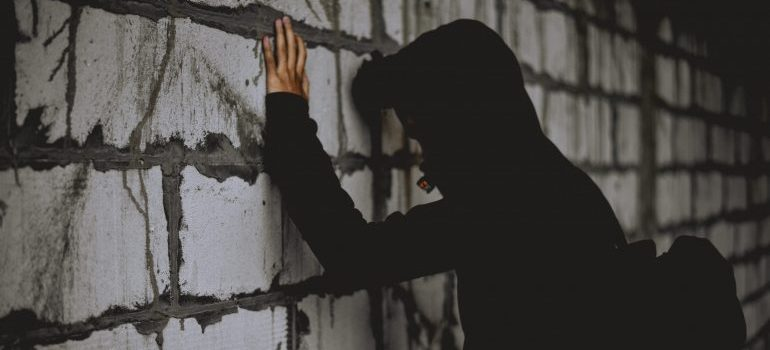 a person in a black hoodie holding hands and their head against the wall