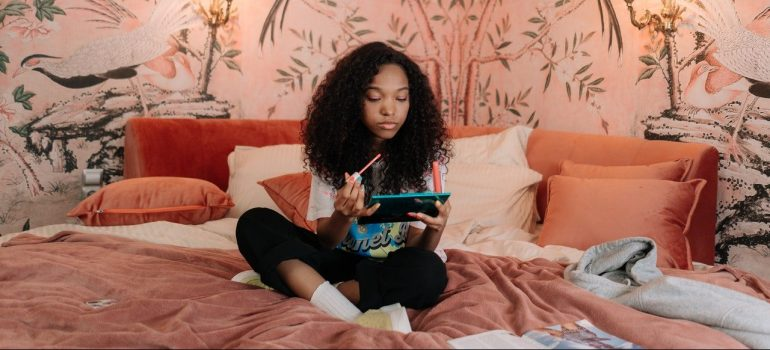 a teenage girl doing makeup on the bed