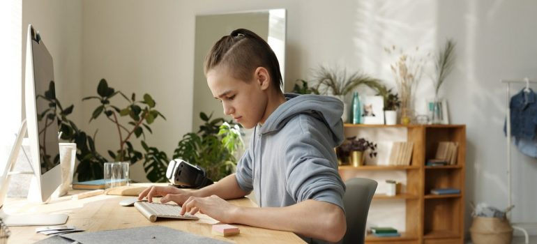 a male child typing something on his PC