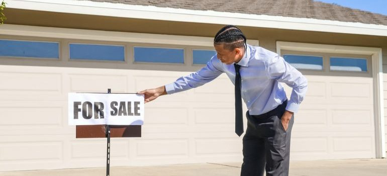 Man in a suit holding sign for sale in front of a house garage.