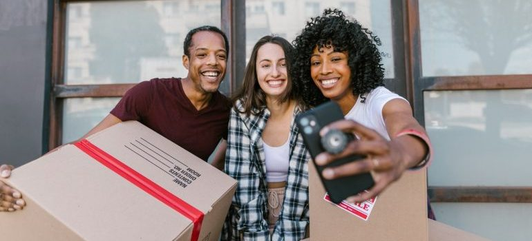 Movers and customers taking a selife with cardboard boxes.