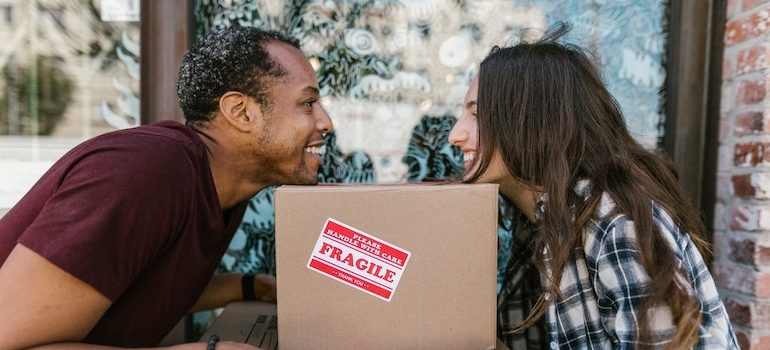 man and woman smiling over a box