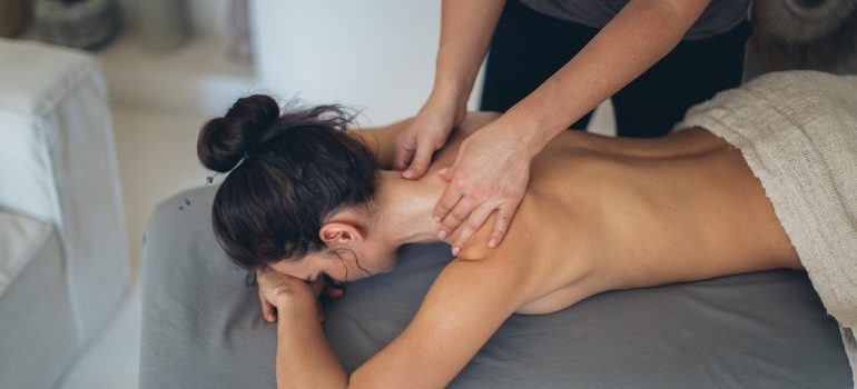A girl laying down while another woman is giving her a massage.