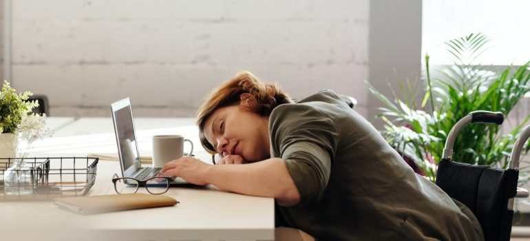 A tired girl sleeping at her table with coffee cup and laptop open.