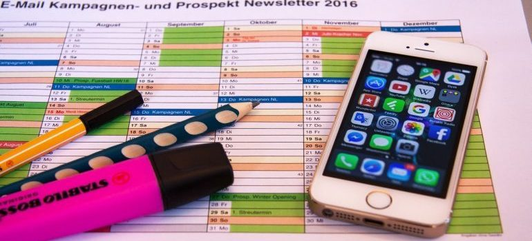 A phone, marker, pen, and pencil layed down on a prospekt newsletter.