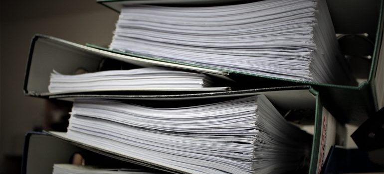 A pile of folders with documents inside.
