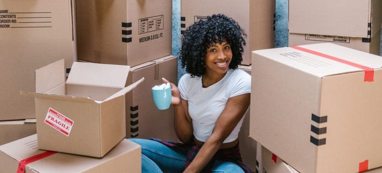 A woman sitting among moving boxes.