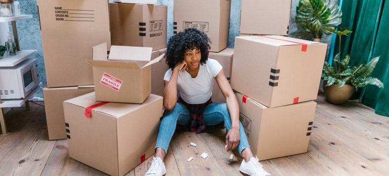 Woman sitting in front of boxes.