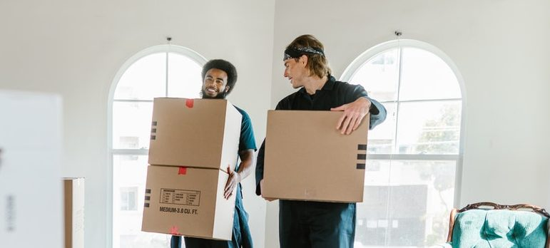 Two movers carrying cardboard boxes