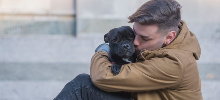 A person hugging a small dog