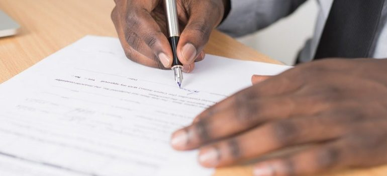 a person signing a paper
