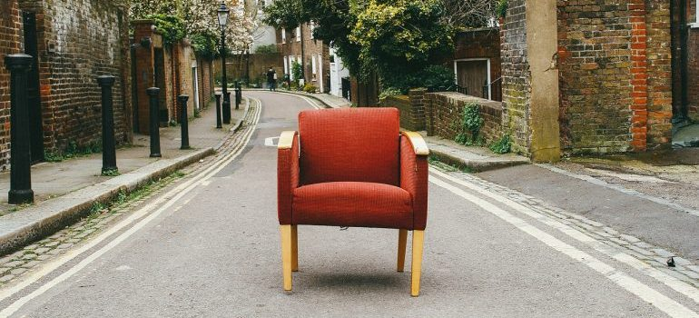A red sofa chair in the middle of the street.