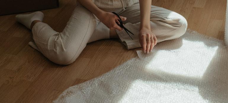 woman cutting bubble wrap