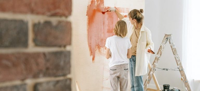 Mother and a child painting the walls in an empty apartment.
