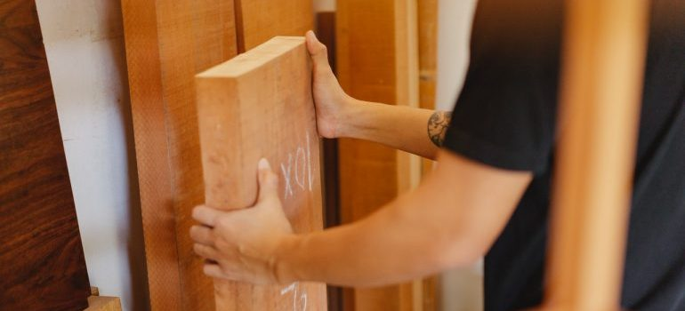 Person holding wooden boards.