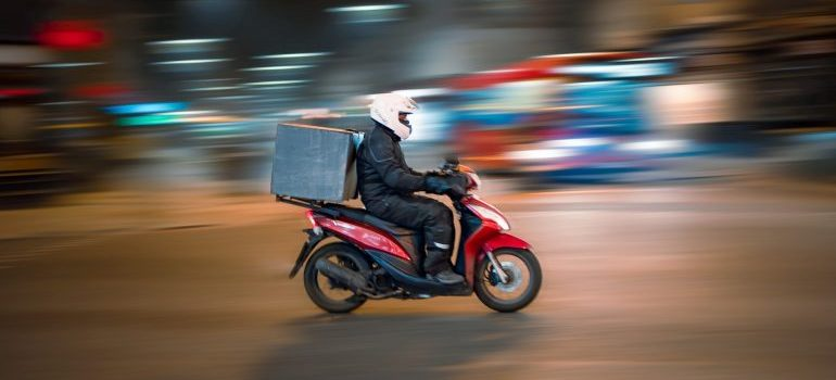 A person on the motorcycle and a package on the back, driving through the city