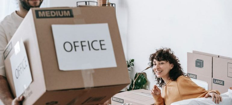 A man and a woman packing office.
