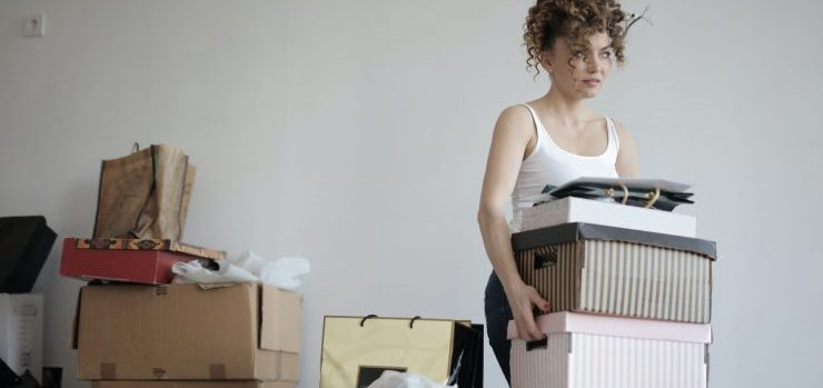 girl packing and carrying boxes, preparing to find storage on a student budget