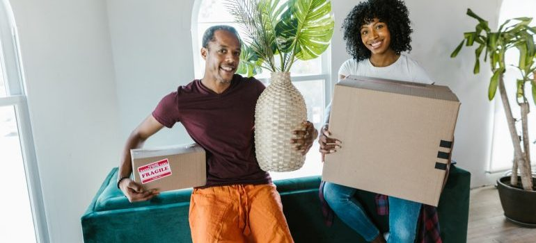 two people holding cardboard moving boxes,